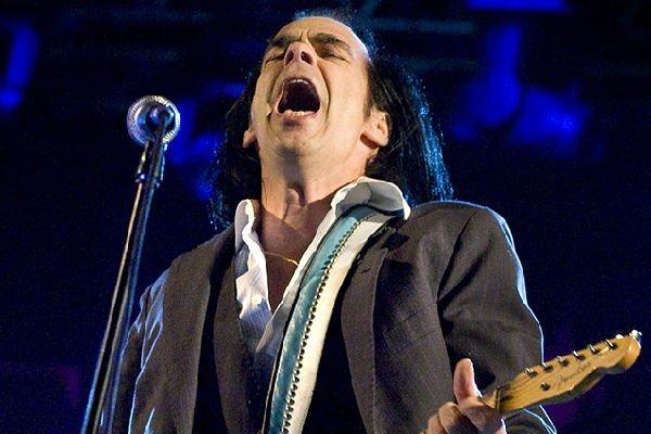 Nick Cave cade dal palco a un concerto